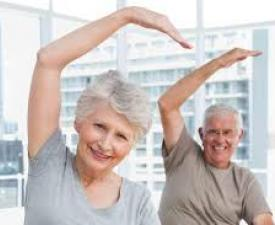 Two older adults stretching arm over their heads
